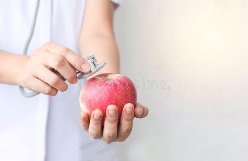 Untersuchungsapfel Arztfrau mit Stethoskop Konzept von Naturkostdiätnahrung und von gesundem Lebensstil stockfotografie