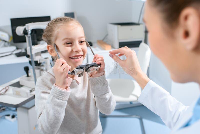 Untersuchungsaugen des Optometrikers kindermit Proberahmen lizenzfreies stockbild