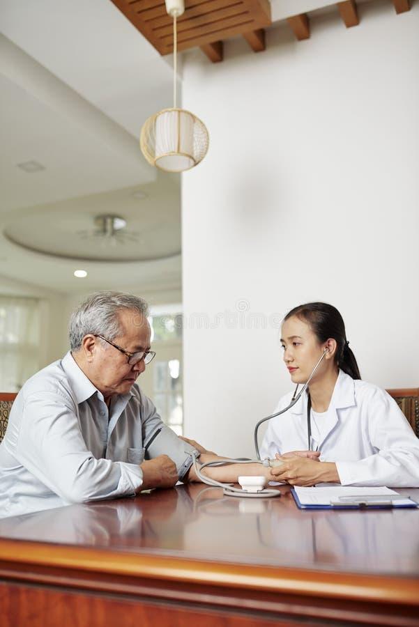 Untersuchungsblutdruck Doktors des Patienten stockbild
