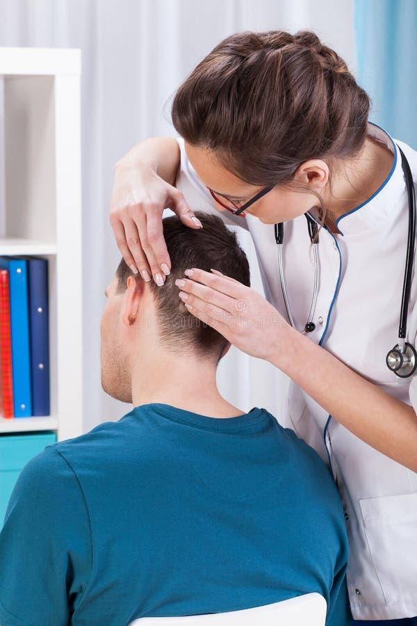 Untersuchungspatient jungen Doktors stockbild