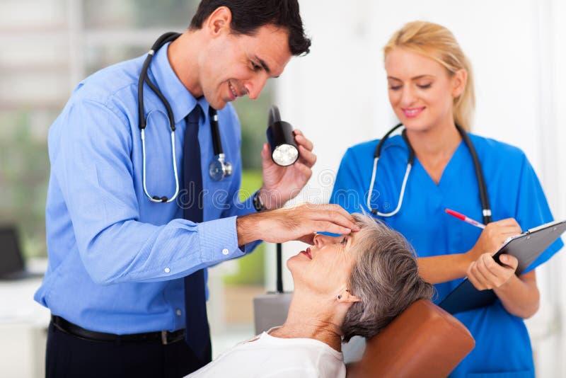 Untersuchungssenior des Augenarztes stockfotos