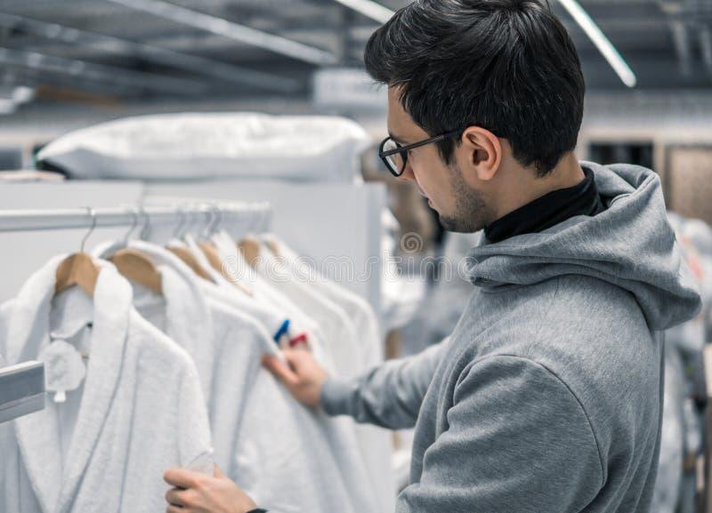 Untersuchungsund kaufender Bademantel des männlichen Kunden im Supermarkt stockfoto