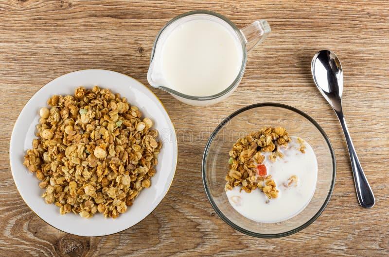 Untertasse mit muesli, Schüssel mit Granola und Jogurt, Krug Jogurt, Löffel auf Holztisch Beschneidungspfad eingeschlossen lizenzfreie stockbilder