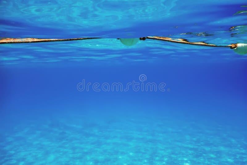 Unterwasseransicht-Bojen-Seil-Sperre, Sicherheits-Wasser-Bojen setzen auf den Strand lizenzfreies stockbild