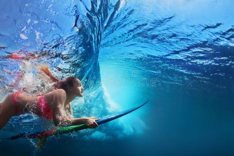Unterwasserfoto des Surfermädchentauchens unter Meereswogen stockfotografie