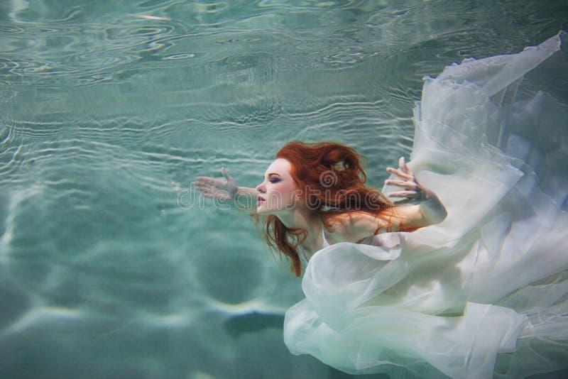 Unterwassermädchen Schöne rothaarige Frau in einem weißen Kleid, schwimmend unter Wasser lizenzfreies stockbild