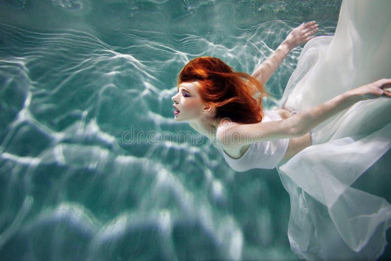 Unterwassermädchen Schöne rothaarige Frau in einem weißen Kleid, schwimmend unter Wasser lizenzfreie stockbilder