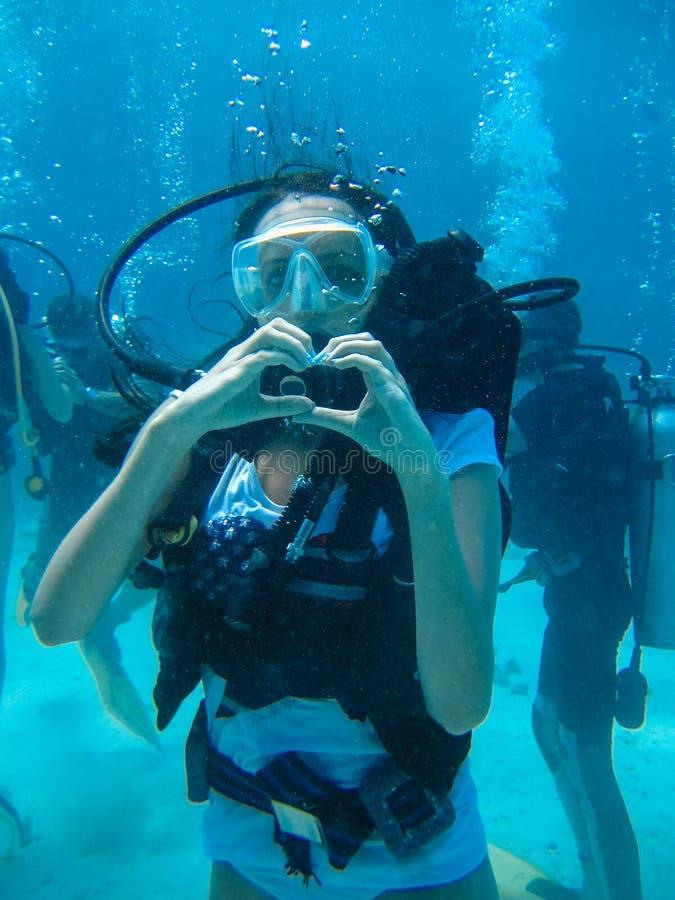 Unterwassertrieb eines Frauentauchens und Vertretung lieben Signal lizenzfreie stockfotografie