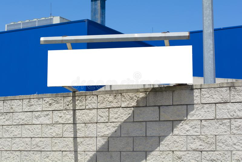 Unterzeichnen Sie auf der Steinwand, leere Anschlagtafel auf blauer Wand lizenzfreies stockbild