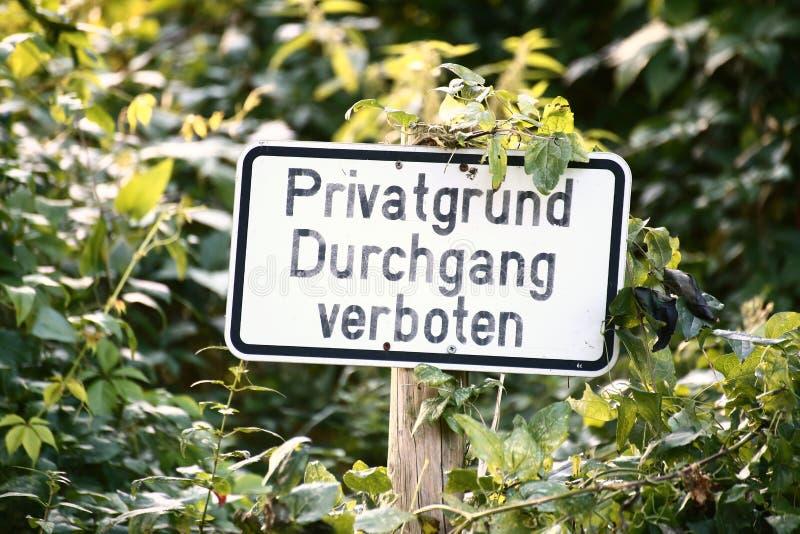 Unterzeichnen Sie herein einen überwucherten Platz in Deutschland Es sagt Privateigentum, kein Übertreten stockfotografie
