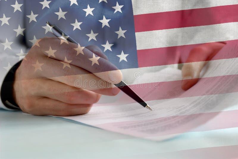 Unterzeichnende Papiere des Geschäftsmannes mit US-Flaggenüberlagerung lizenzfreie stockfotografie