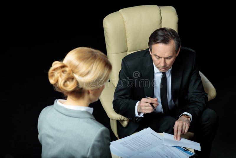 Unterzeichnende Papiere des reifen Geschäftsmannes und der blonden Geschäftsfrau lizenzfreie stockfotografie