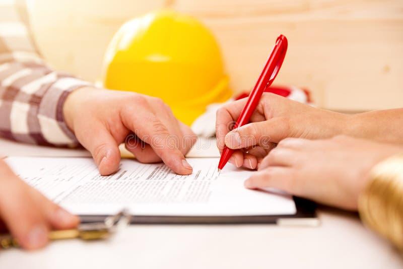 Unterzeichnender Bauauftrag der Frau mit Auftragnehmer, ein Haus zu bauen stockbild
