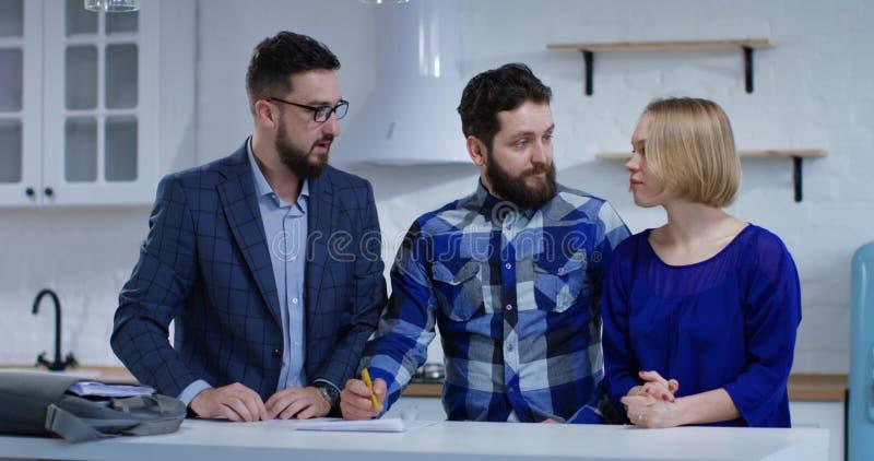 Unterzeichnender Eigentumsvertrag des Ehemanns mit seiner Frau stockfoto