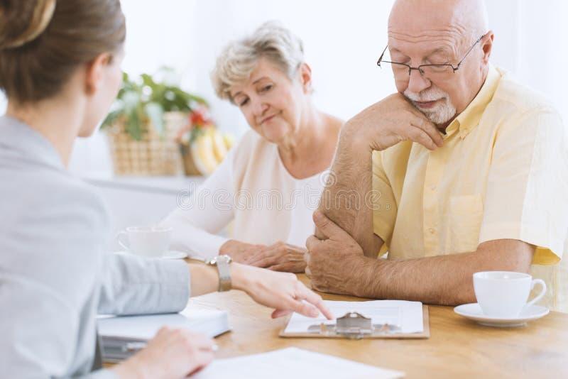 Unterzeichnender Vertrag der älteren Leute stockfotos
