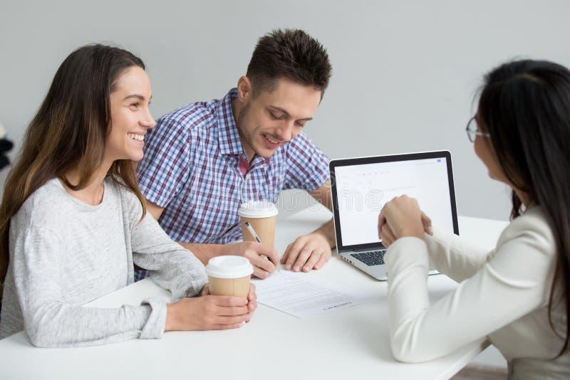 Unterzeichnender Vertrag des glücklichen Paars, der Darlehen bei der Sitzung mit Bank w nimmt lizenzfreies stockfoto