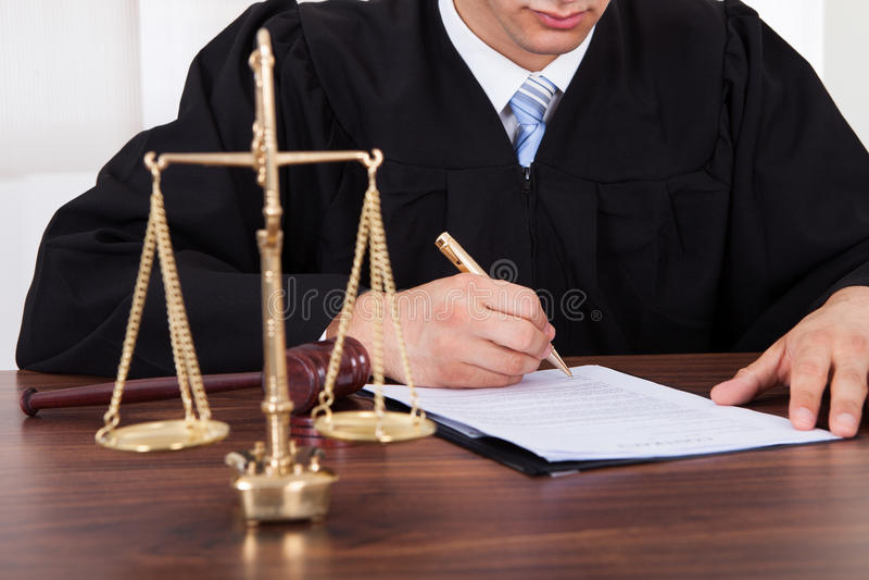 Unterzeichnendes Dokument des Richters bei Tisch im Gerichtssaal lizenzfreie stockfotografie