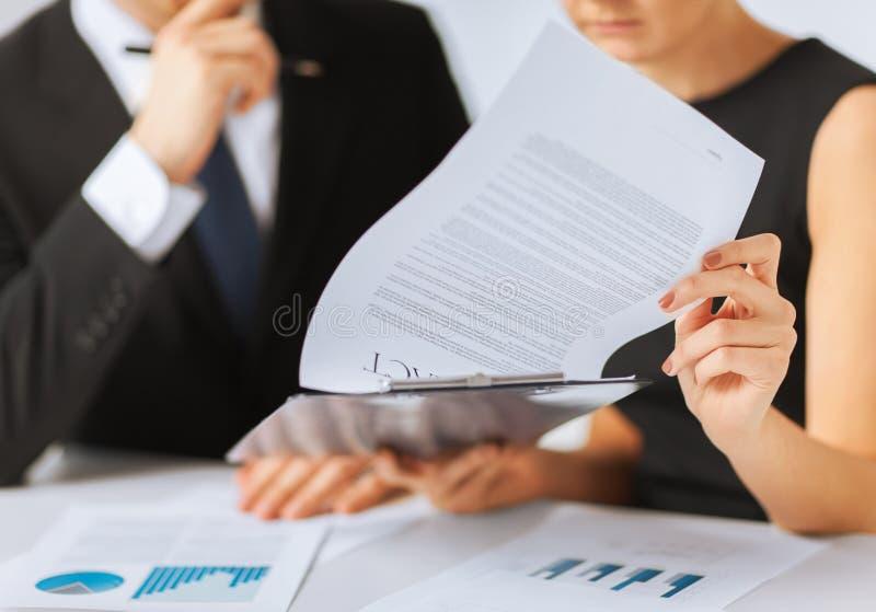 Unterzeichnendes Vertragspapier des Mannes und der Frau stockbild