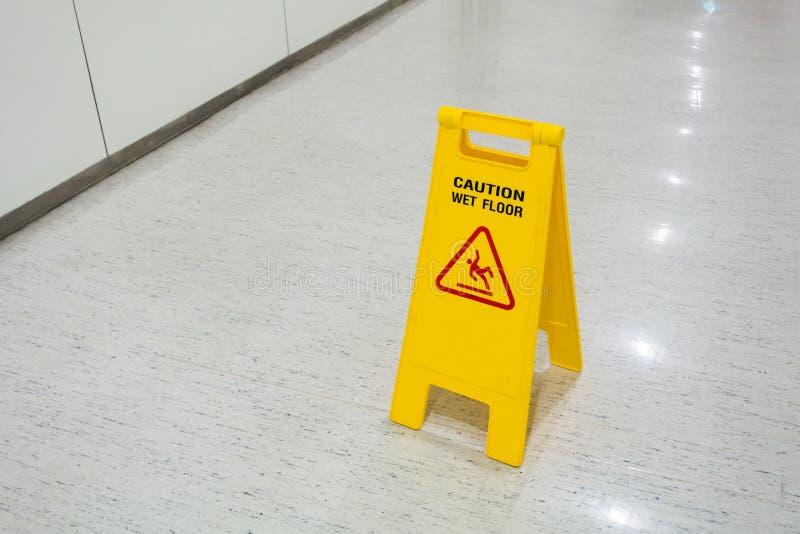 Unterzeichnet gelben gesetzten an nassen Plastikboden der Bodentext-Vorsicht lizenzfreie stockfotografie