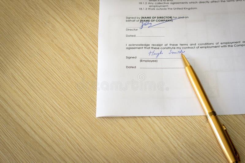 Unterzeichneter Anstellungsvertrag auf Schreibtisch stockfotos