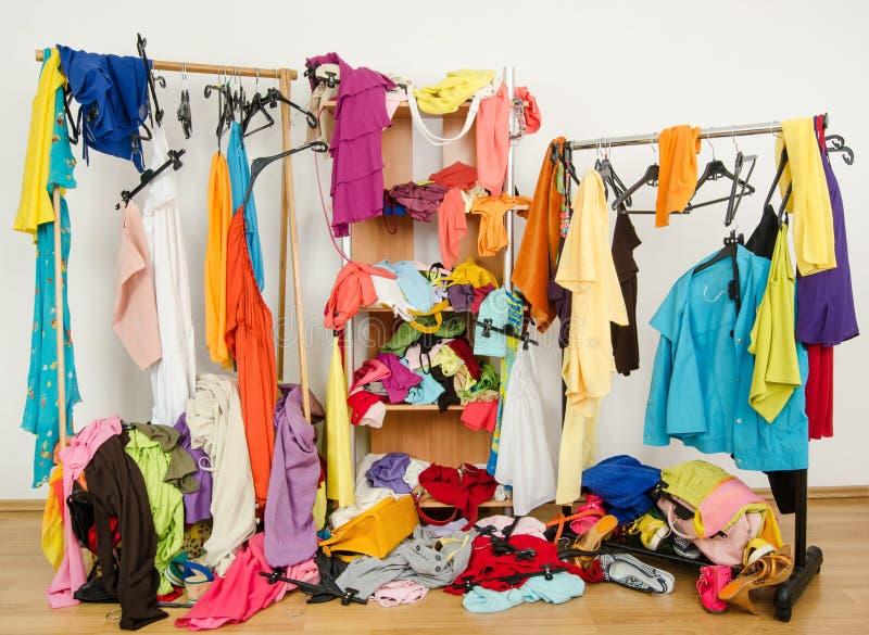 Untidy созданный суматоху шкаф женщины с красочными одеждами и аксессуарами стоковая фотография