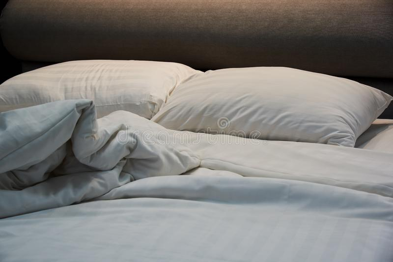 Untidy blanket, pillows on the bed royalty free stock images