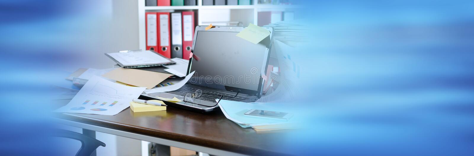 Untidy and cluttered desk; panoramic banner. View of an untidy and cluttered desk; panoramic banner royalty free stock images