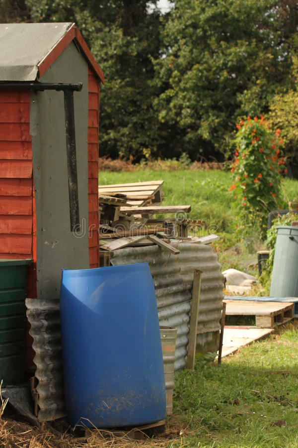 Untidy garden. Shed and allotment plot with roof sheets, wooden pallets and water containers royalty free stock photography
