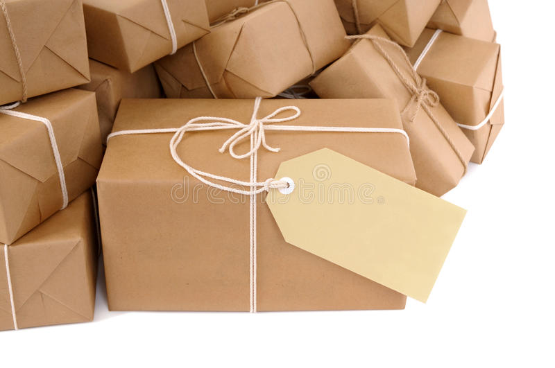 Brown paper package with blank manila label isolated on white stock image