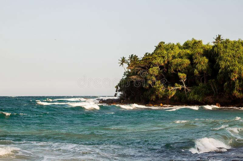 Untouched tropical beach with rocks in the water and white waves in Sri Lanka.  stock photos