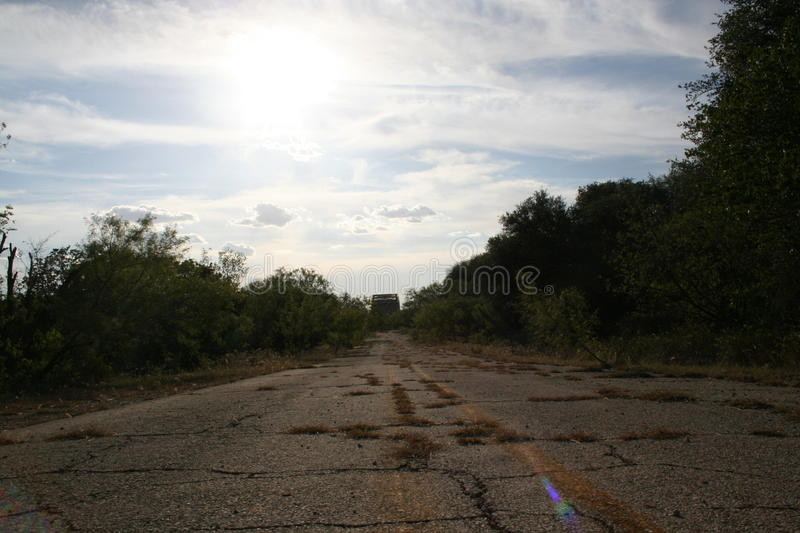 Untraveled road. An old road leading to an inaccessible bridge stock photos