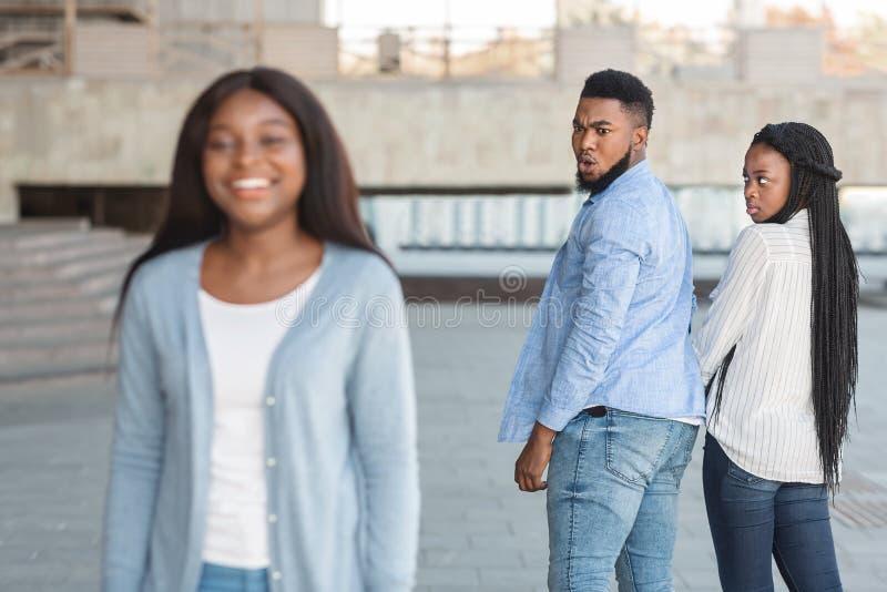 Untreuer Kerl starrte eine andere Frau an, während er mit einer Freundin im Freien spazierte lizenzfreie stockfotos