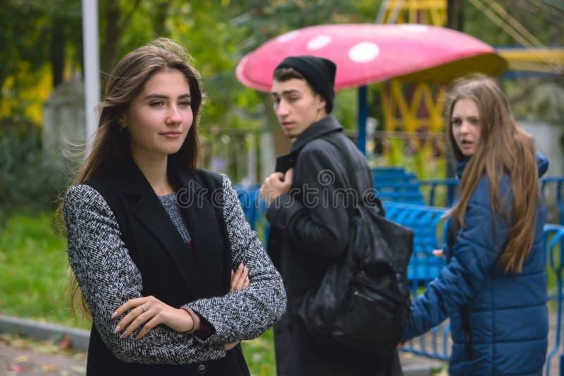 Untreuer Mann, der mit Freundin geht und einem anderen verlockenden Mädchen überrascht betrachtet lizenzfreies stockbild