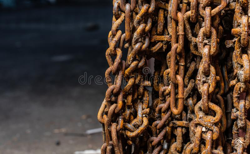 Unused and rusty snow chains hanging from a wall royalty free stock photo