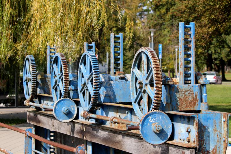 Unused small dam cogwheels rusted gears in a single row with cracked dilapidated paint mounted on metal beam with strong bolts. On warm sunny day royalty free stock images