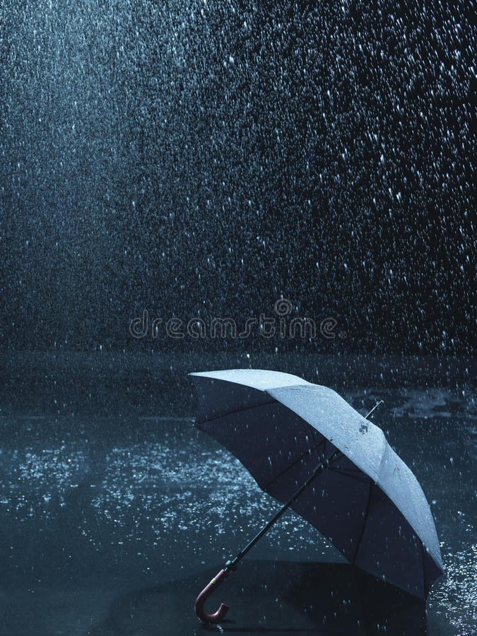 Unused umbrella lying on ground being rained upon royalty free stock photos