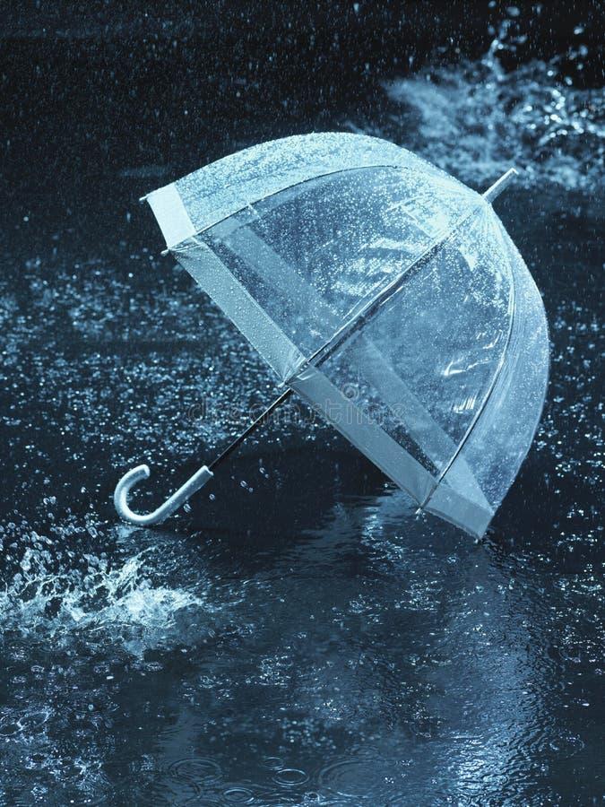 Unused umbrella lying on ground being rained upon stock photos