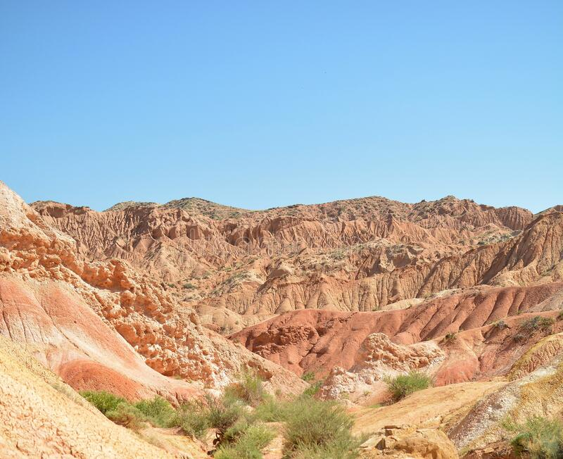Unusual beautiful nature of the canyon in Kyrgyzstan. Red mountains against the blue sky. stock image