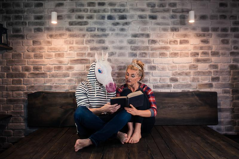 Unusual couple reading a book in stylish apartment stock images