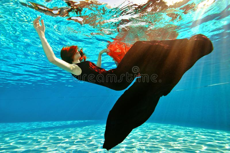 Unusual girl drowns in the pool. A girl with red hair and a dress falls to the bottom of the pool on the background of. Sunlight. Surrealism. Concept. Landscape stock image