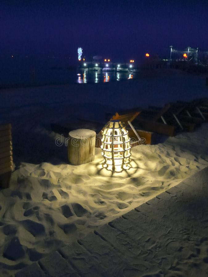 Glowing marine rope lamp on the beach at night royalty free stock photography