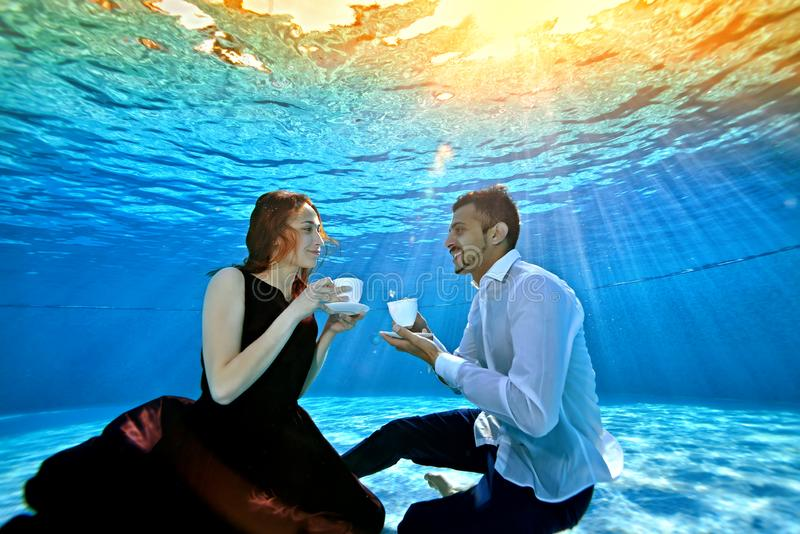 An unusual loving couple, a guy and a girl, look at each other, sitting underwater at the bottom of the pool with white stock photography