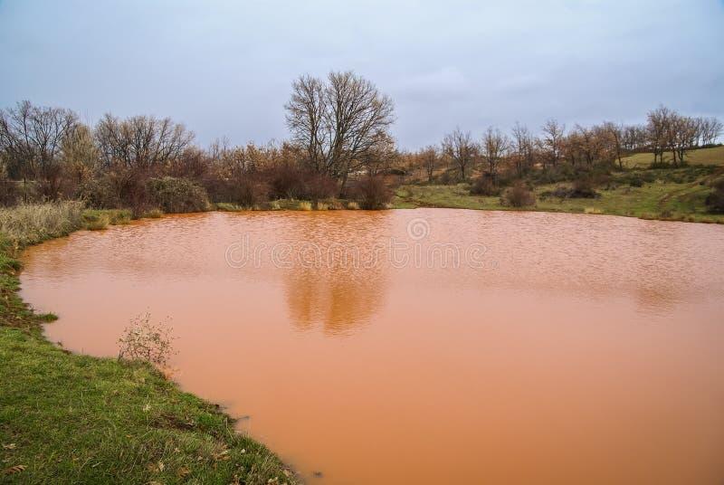 Unusual orange color of the water in the small lake. Pueblos rojos, Castilla y Leon, Spain stock image