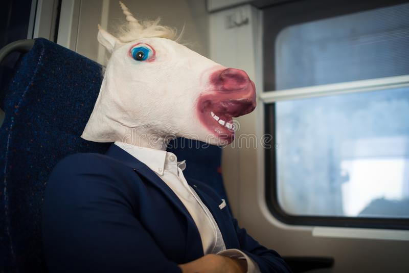 Unusual passenger in elegant suit sits alone inside the train. And ready to travel. Young serious man in comical mask have fun in trip. Funny unicorn traveler royalty free stock photo