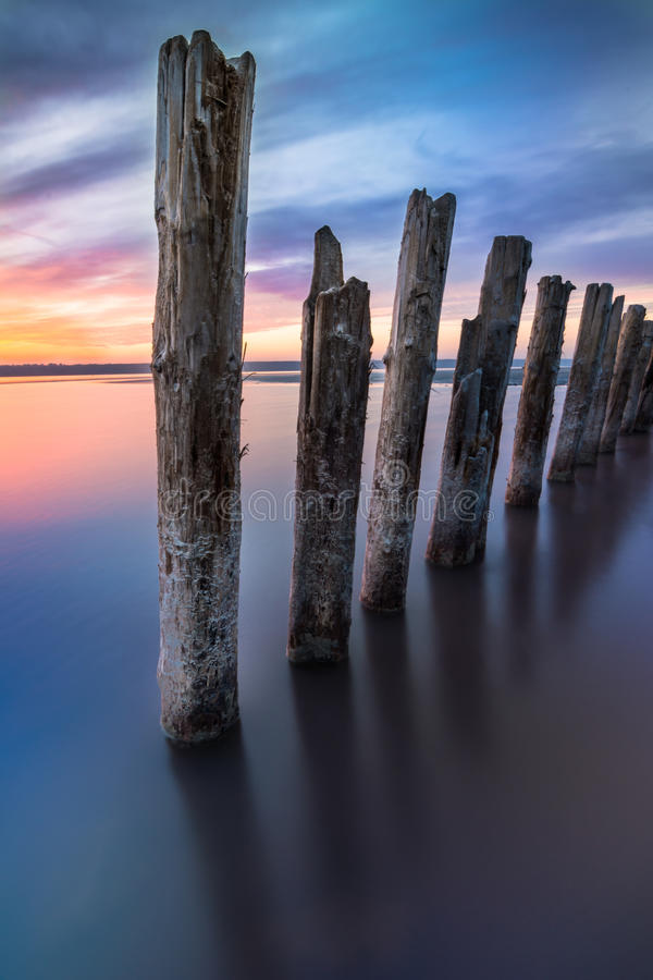 Unusual pillars in the water on the background of colorful sky. With bright clouds royalty free stock photo