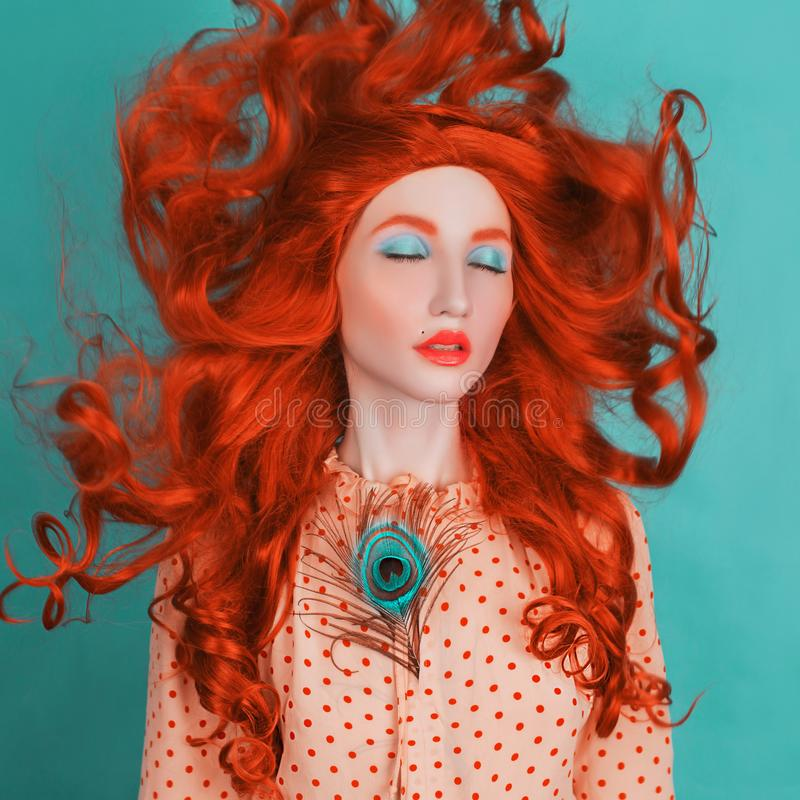 Unusual redhead girl with long curly hair on blue background. Beauty portrait. Hair coloring in salon. Redhead model in yellow stock photo