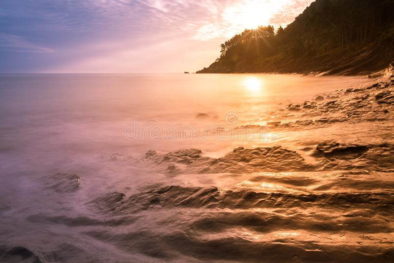 Unusual rock formations turbidites, seashore at sunset. Unusual rock formations turbidites, seashore at orange sunset, Basque Country royalty free stock images