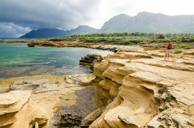 Unusual rocky seacoast of Mallorca. In Natural Park of Levant with rare rock formations, turquoise waters of the Mediterranean, stormy moody sky and a man with royalty free stock images