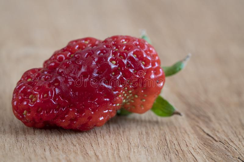 Unusual shaped strawberry on a wooden table stock photos