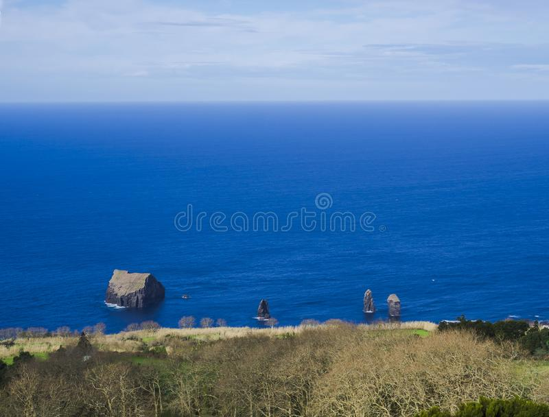 Unusual shaped volcanic rocks formation islets at Mosteiros beach, praia Mosteiros with dried trees coastline and blue stock photos